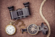 Vintage compass, binoculars, pocket watches on sand background