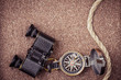 Vintage compass, binoculars on sand background