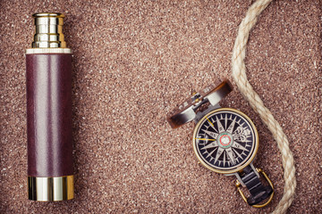 Vintage compass, spyglass on sand background