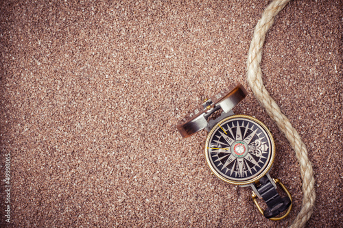 Vintage compass on sand background
