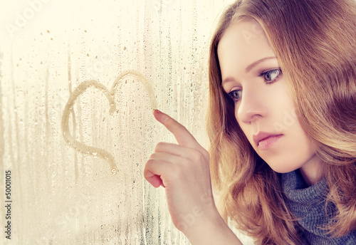 sad girl draws a heart on the window in the rain