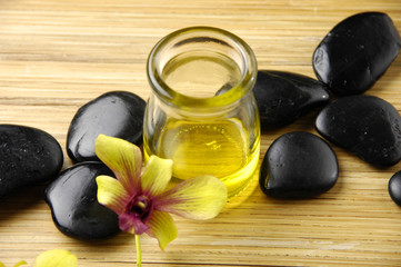 Massage oil and black stones with orchid