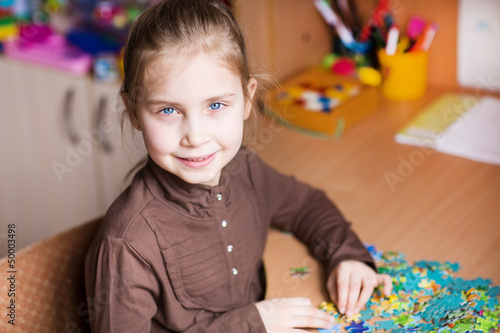 Cute little girl solving puzzles
