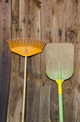 garden tools on wooden house wall background