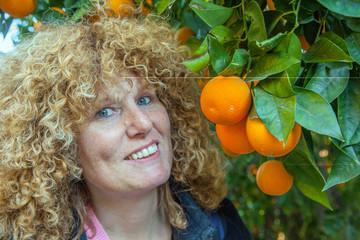 Rothaarige Frau in Orangenplantage