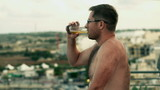 Young man drinking beer on the terrace, slow motion shot 240fps