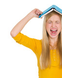 Angry student girl with book over head
