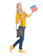Full length portrait of smiling student girl going sideways