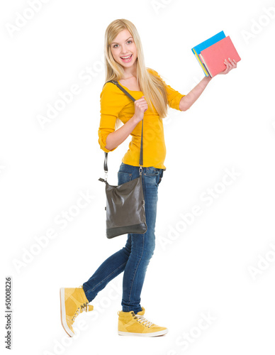 Full length portrait of smiling student girl going sideways