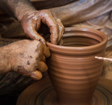Potter hands making in clay on pottery wheel