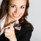 Businesswoman pointing finger at viewer, over gray