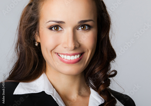 Happy smiling young businesswoman, on gray