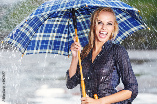 Beautiful blonde woman holding umbrella out in the spring rain