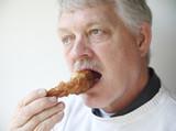 senior man eating fried chicken leg