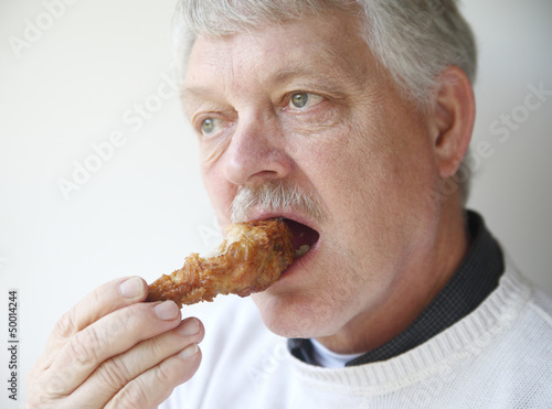 senior man eating fried chicken leg