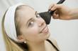 Femme avec un pinceau sur le visage