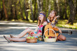 Hippie girls with guitar sitting on the road