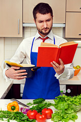 concentrated young man reading cookbook