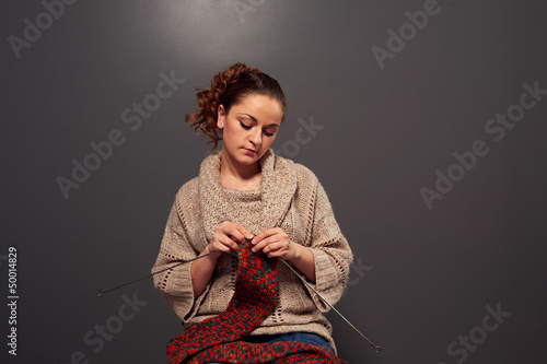 young woman is knitting