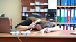 Tired woman sleeping on keyboard at work and trying to speak on