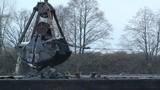 Dredge bucket unloads its contents into a floating barge.