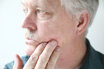 older man with a red, itchy rash on his cheek