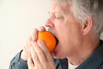 older man bites into orange to start the peeling process