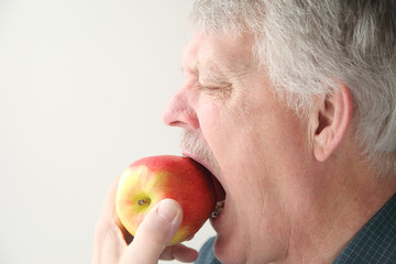 older man bites into an apple