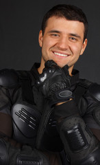 Man in a bikers uniform is smiling during the photoshoot