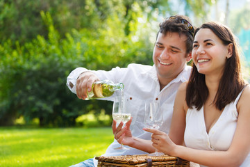 Young happy couple enjoying a glasses of white wine