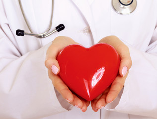 Female doctor standing with stethoscope and red heart symbol
