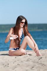 Beautiful woman applying suntan lotion at beach