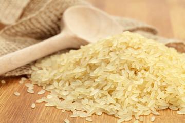 Ungekochter Reis und Holzlöffel