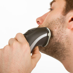 Young man shaving his beard off
