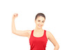 Young smiling woman showing her bicep muscle