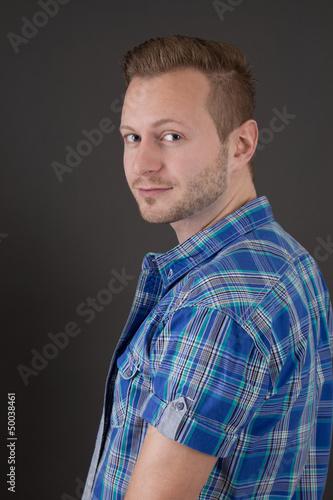 Schöner junger Mann mit blauen Augen in kariertem Hemd