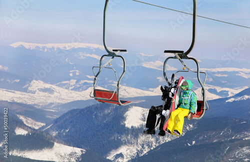 Snowboarders couple on a ski lift