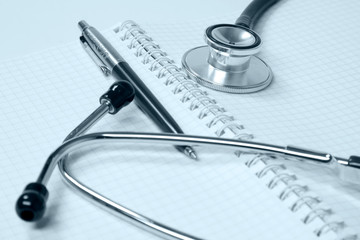 Stethoscope on medical billing statement on table,