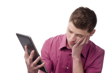 Man acting tired and bored from reading on the tablet.