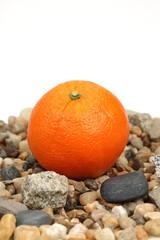 Pomarańcza na kamykach na białym tle.