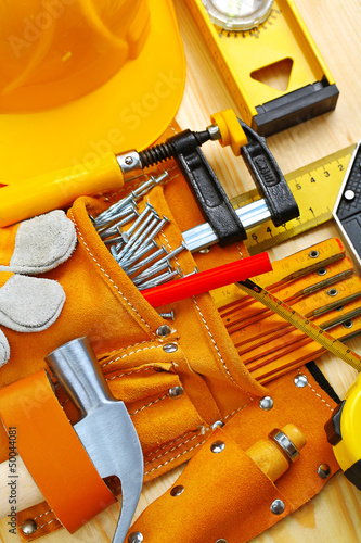 building tools in belt and hardhat