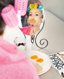 Woman with sausages on a fork simulating lip enhancement poster