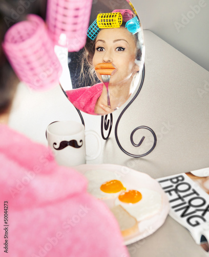 Woman with sausages on a fork simulating lip enhancement