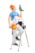 A young worker on a ladder holding a driller