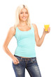 Beautiful young female holding a glass of orange juice and posin