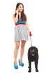 Full length portrait of a female walking her dog and talking on