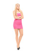 Full length portrait of an attractive woman posing  in a pink dr