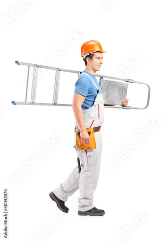 Full length portrait of a repairman with a helmet carrying a lad