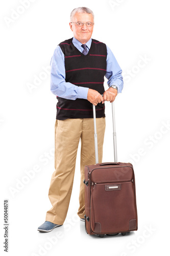 Full length portrait of a senior gentleman standing with a trave