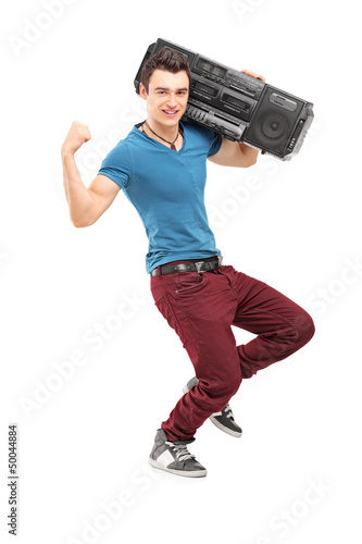 Full length portrait of a young muscular man posing with a radio